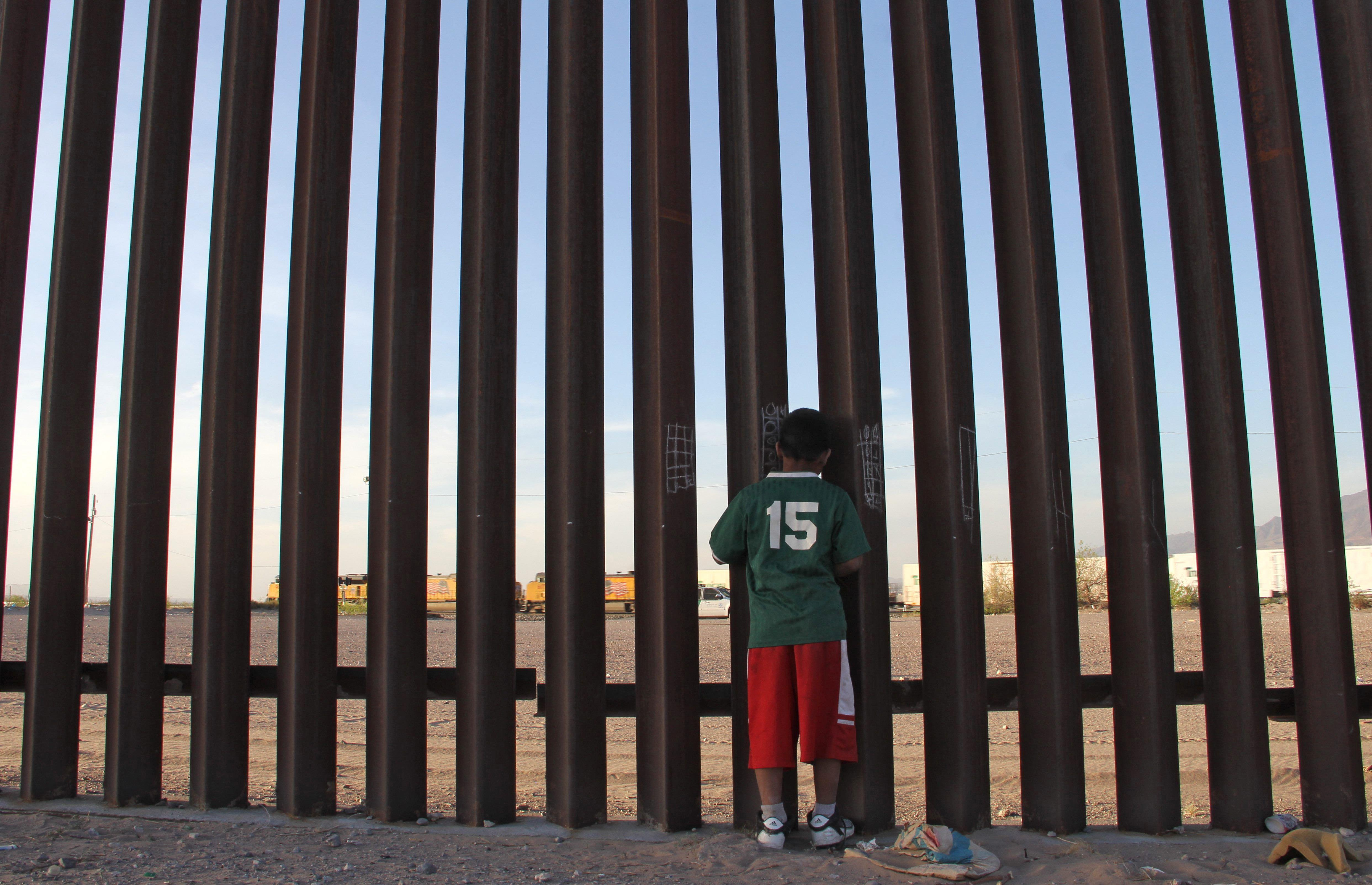 A Mexican child looks at a vehicle of the US border patrol through the US-Mexico fence in Ciudad Juarez, Chihuahua state, Mexico on April 4, 2018.